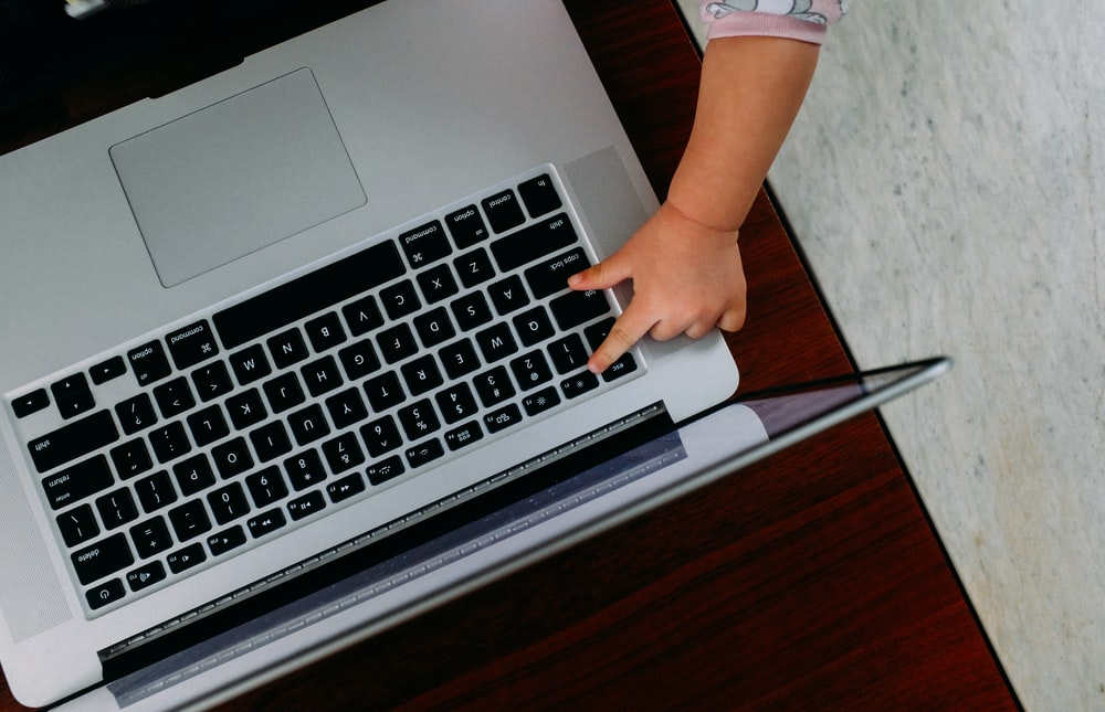 baby's hand reaching out to macbook pro on brown wooden table