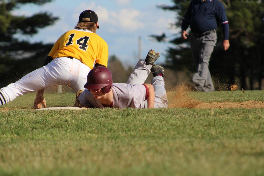 2 men in white and brown baseball jersey shirt and pants playing baseball during daytime