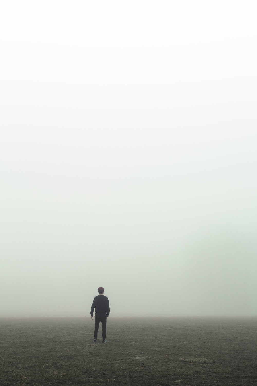 man in black jacket standing on foggy weather