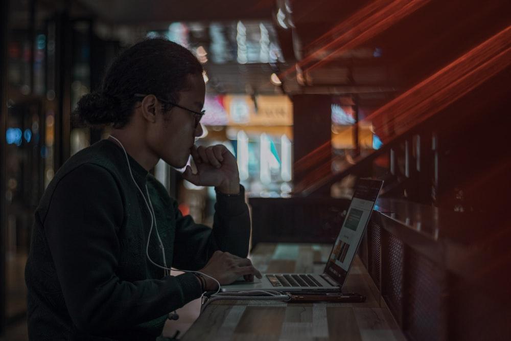 man in black jacket using laptop computer