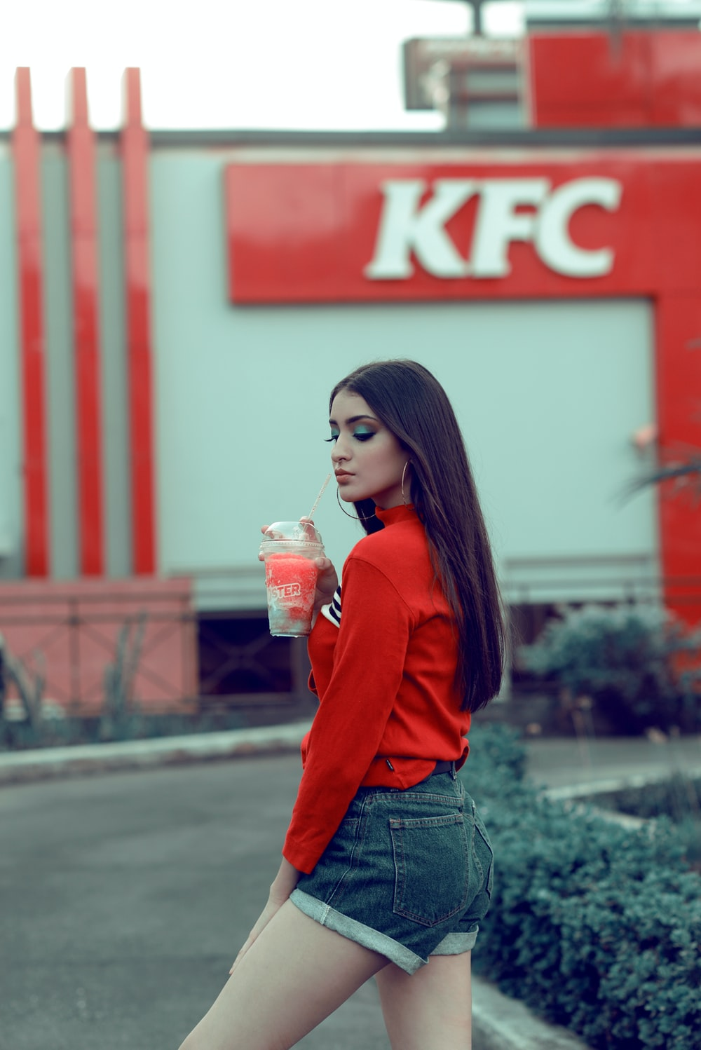 woman in red long sleeve shirt holding clear plastic cup
