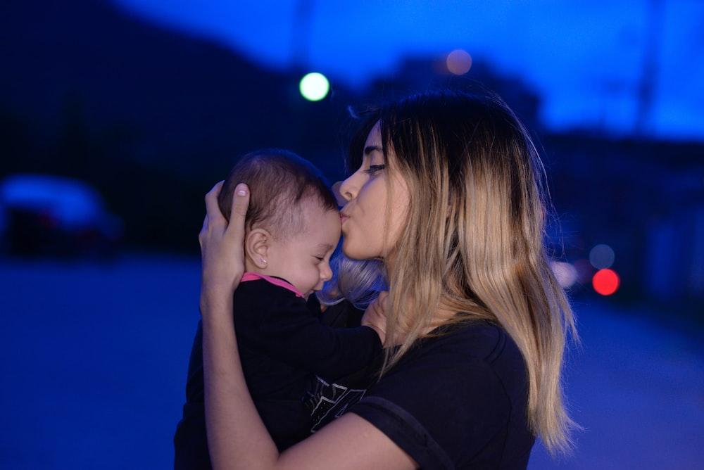woman in black shirt kissing womans cheek