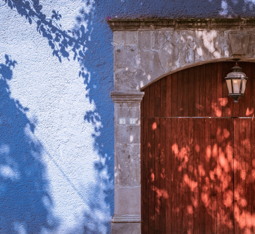 brown wooden door on blue and white wall