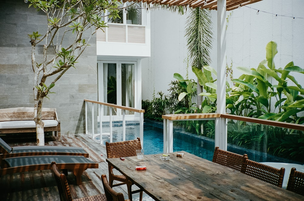 brown wooden table with chairs near swimming pool