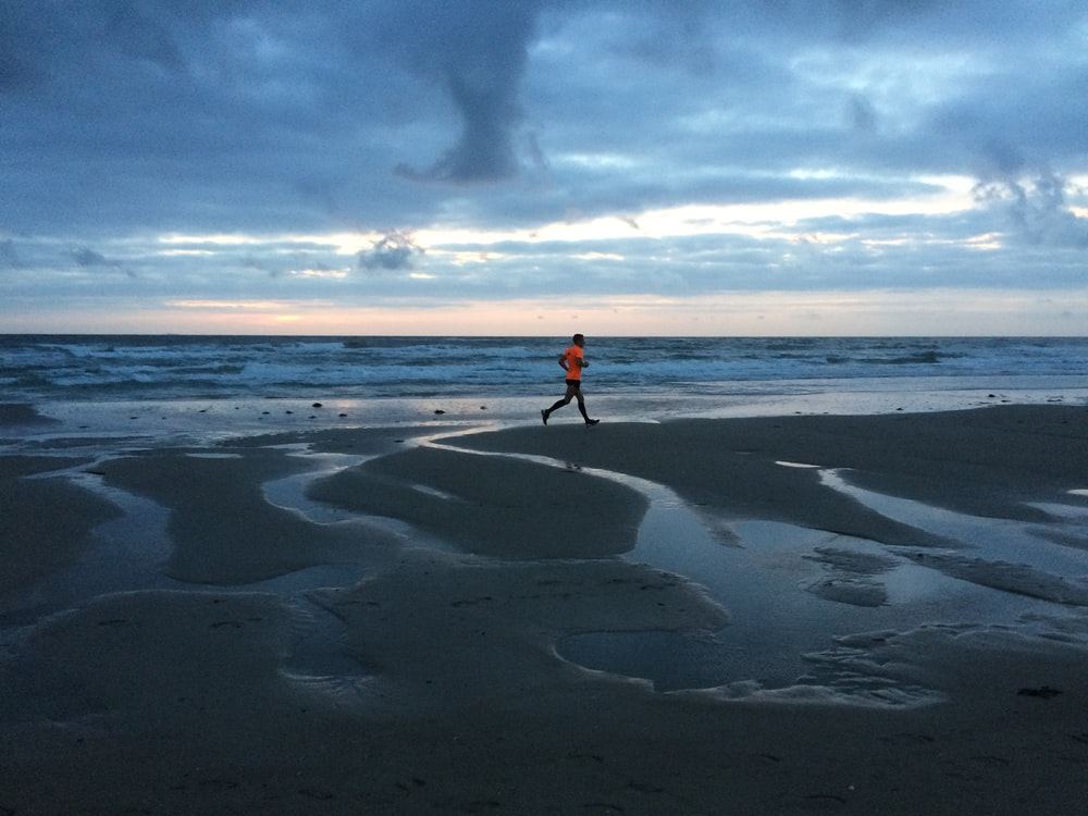 man in orange shirt and blue denim jeans walking on beach during daytime