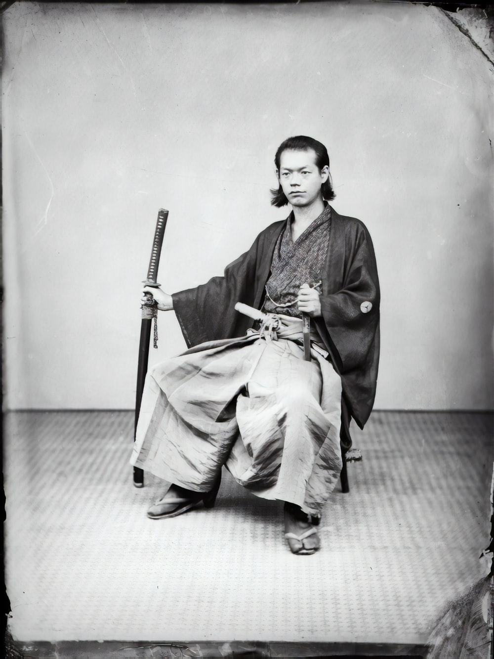 man in black coat and pants sitting on chair