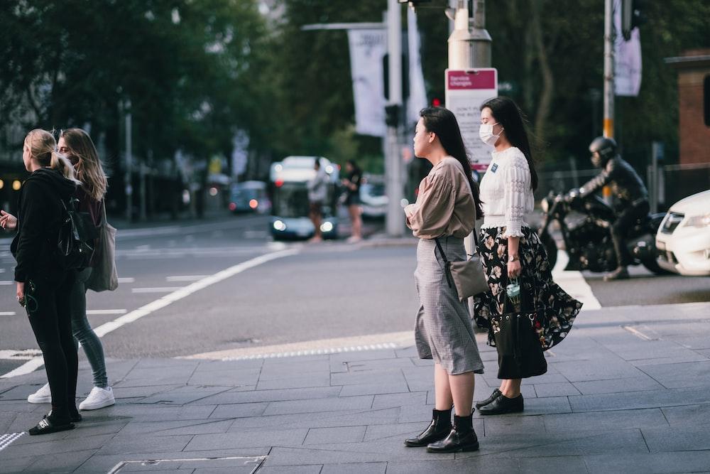 woman in beige coat standing on sidewalk during daytime