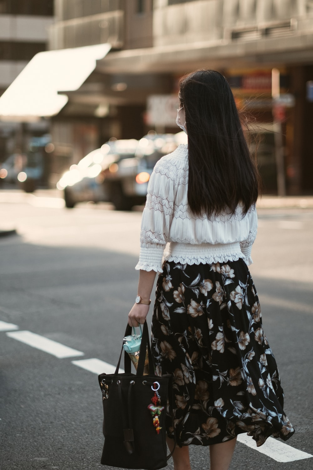 woman in white long sleeve shirt and black floral skirt standing on sidewalk during daytime