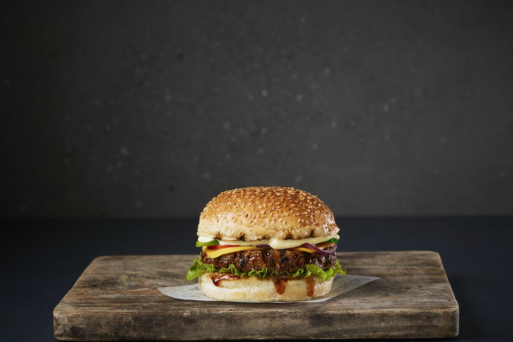 burger on brown wooden chopping board