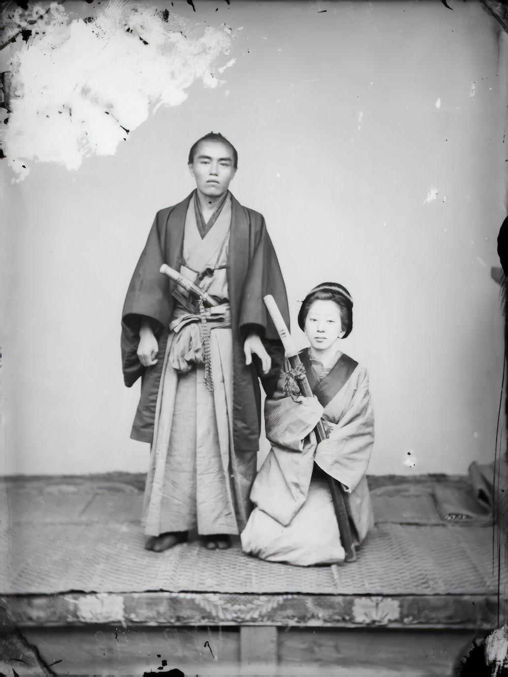 woman in kimono standing beside boy in thobe