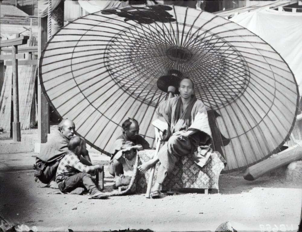 grayscale photo of 2 women and 2 children under umbrella