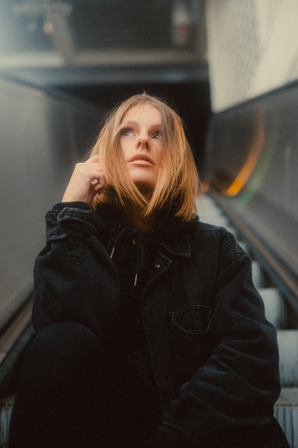woman in black leather jacket sitting on train