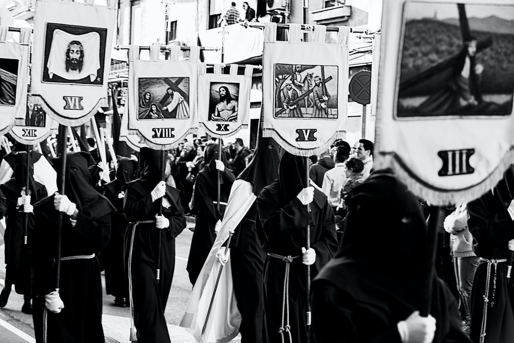 people in black robe standing in front of white and black wall