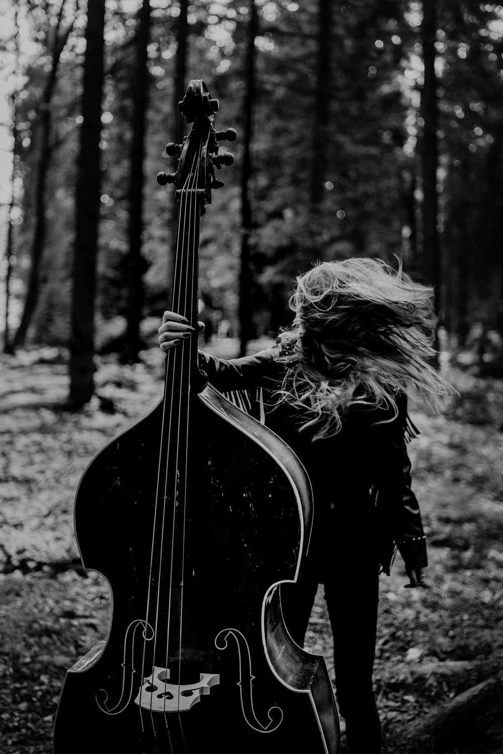 woman in black long sleeve dress playing guitar in grayscale photography