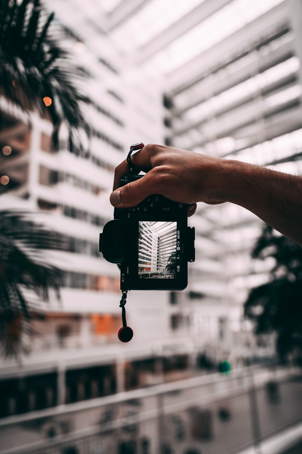 person holding black smartphone taking photo of building during daytime