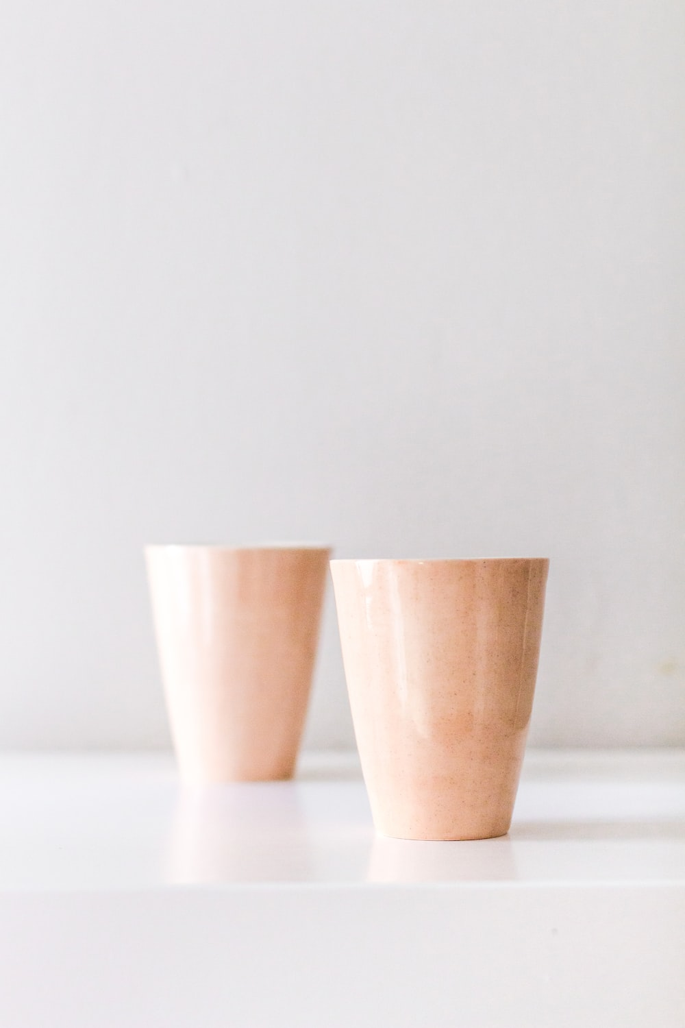 2 brown plastic cups on white table