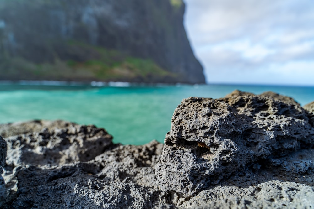 black and gray rock formation near body of water during daytime