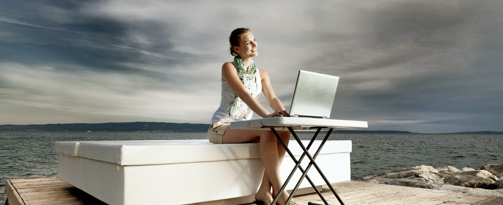 woman in white tank top sitting on white chair using macbook