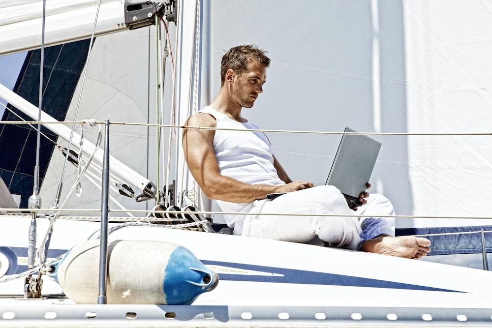 man in white tank top sitting on white boat during daytime