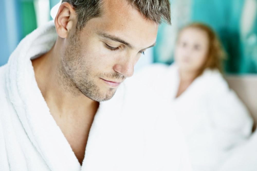 man in white robe beside woman in white shirt