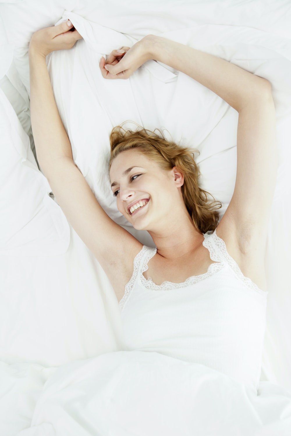 girl in white tank top lying on bed