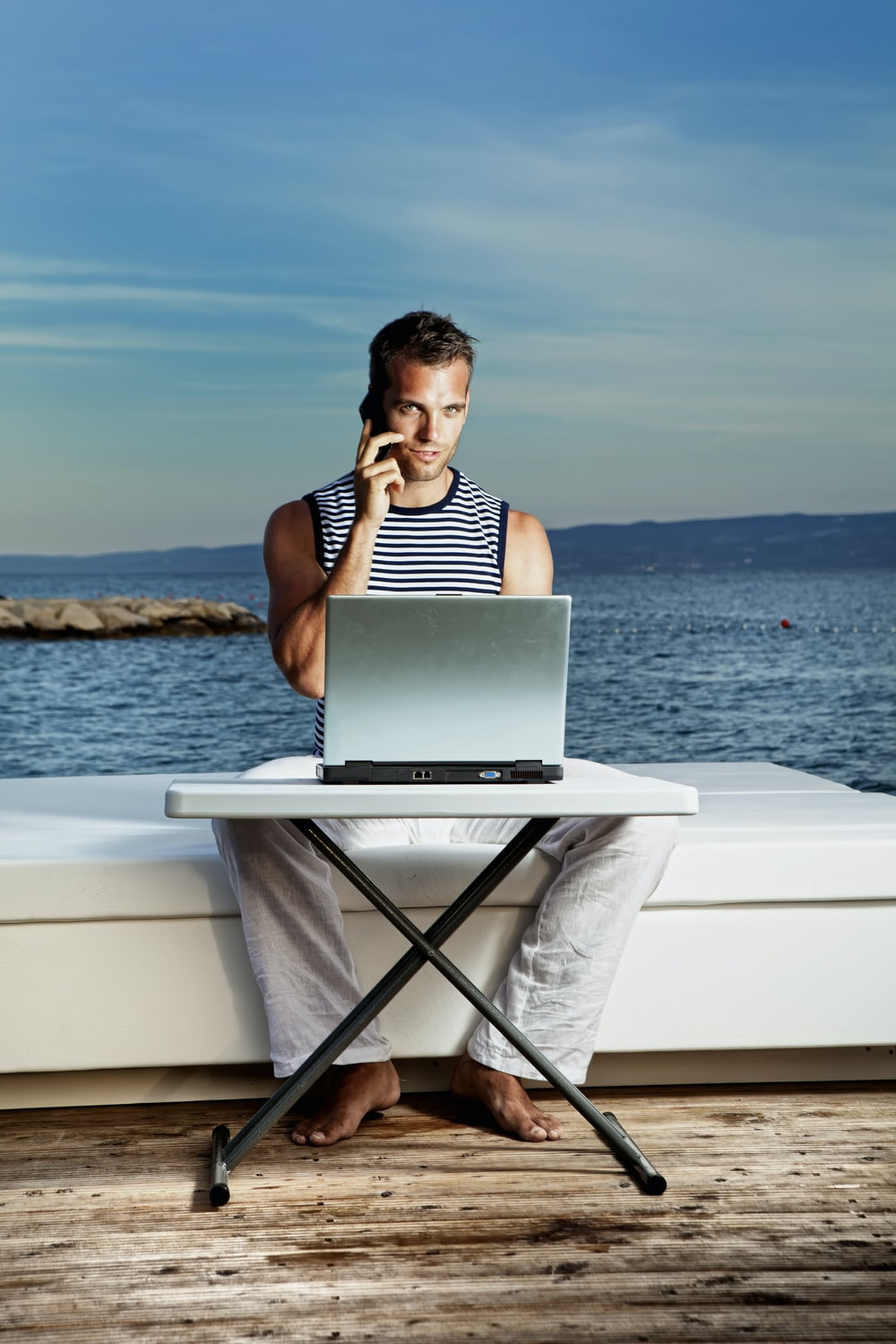 woman in black and white stripe tank top sitting on white chair using macbook air