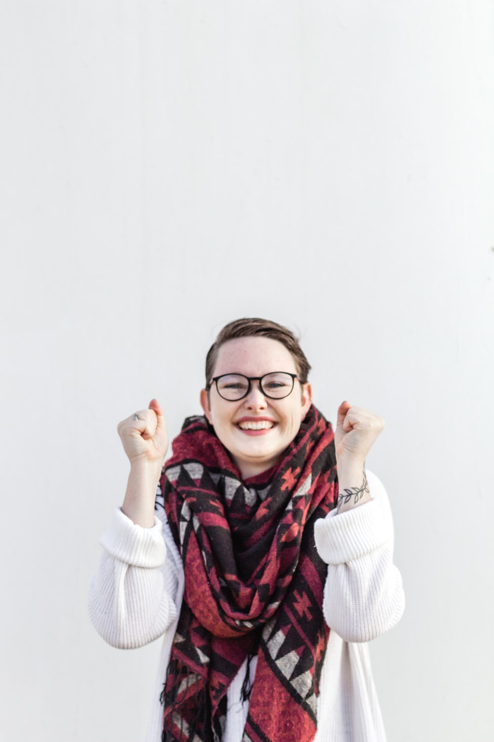 woman in white sweater wearing red scarf and black framed eyeglasses