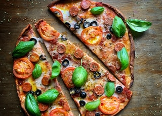 pizza with green leaves on brown wooden table