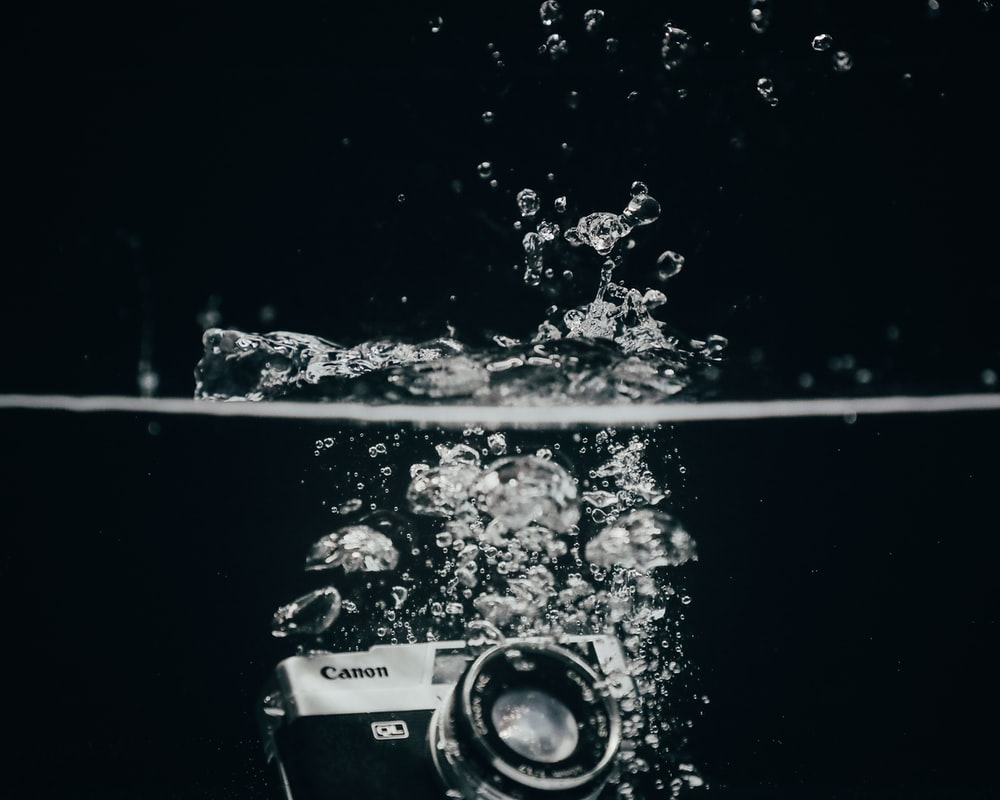 black and silver dslr camera on glass