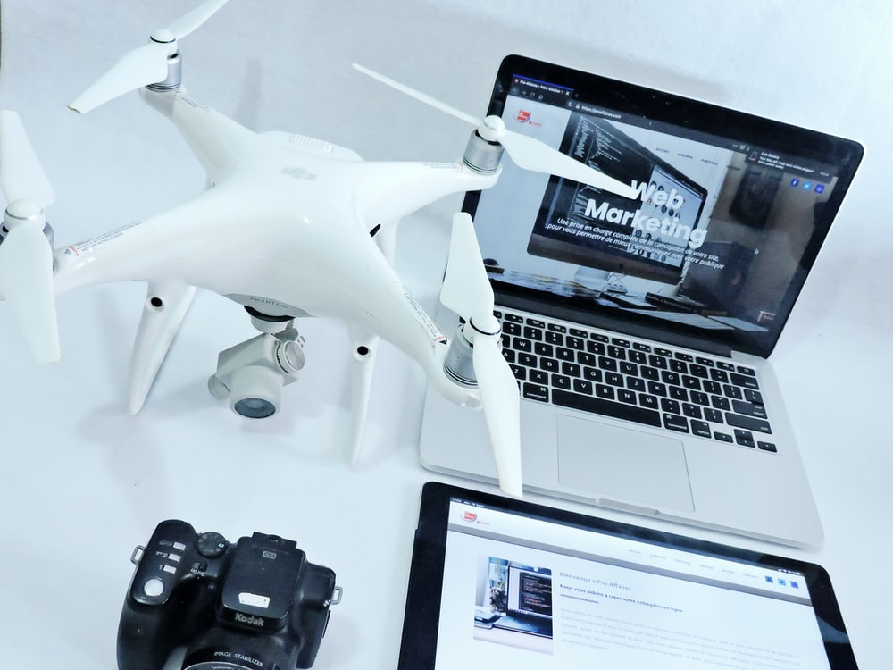 white and black drone near black and silver laptop computer