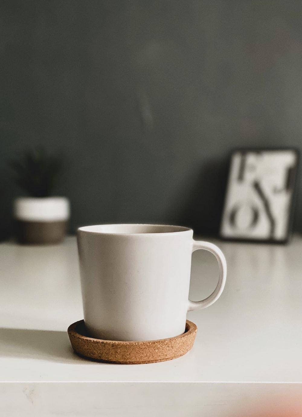 white ceramic mug on brown coaster