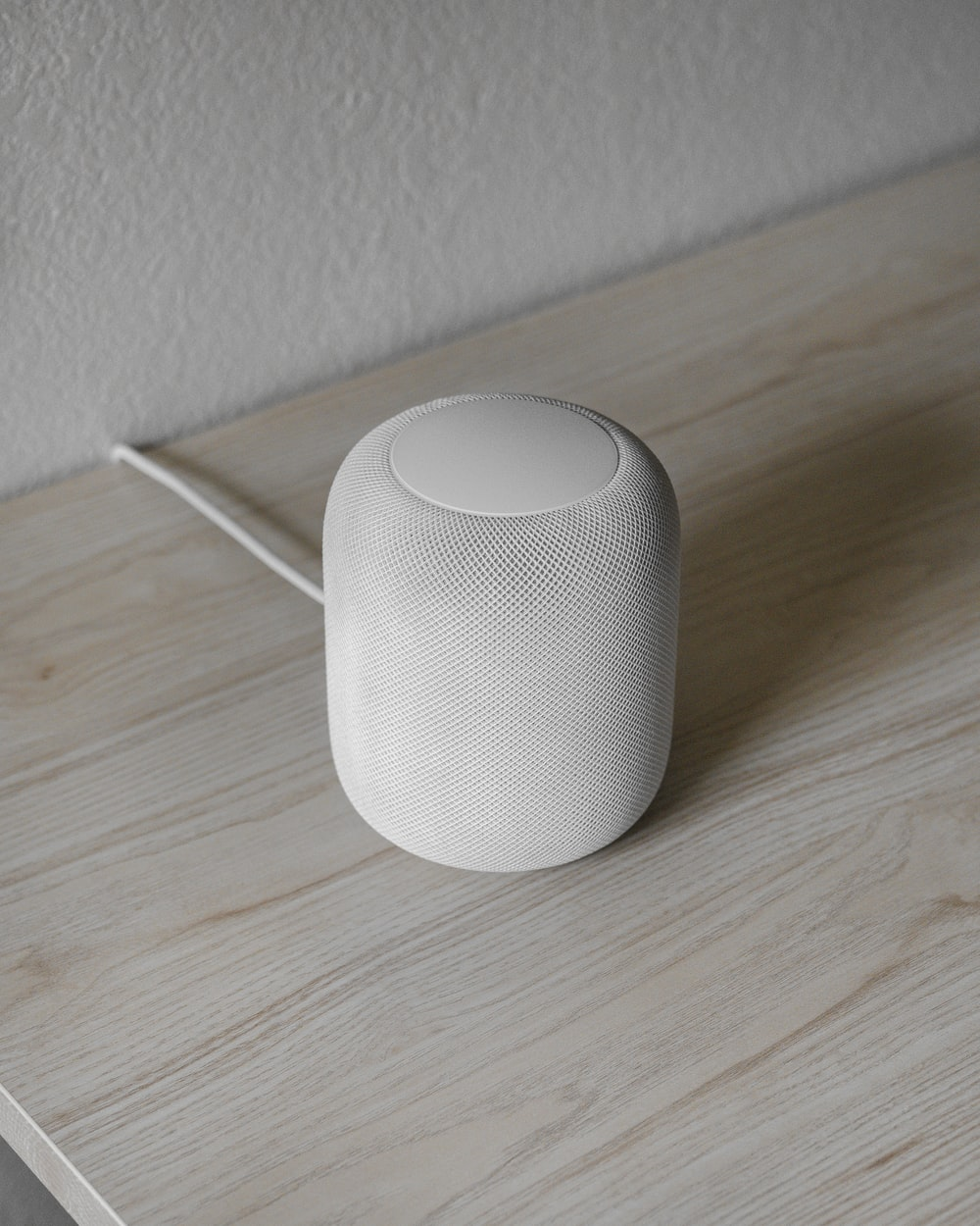 white round portable speaker on brown wooden table