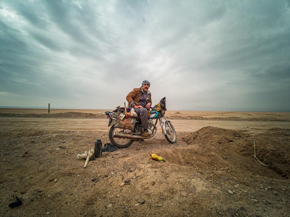 man in orange jacket riding on bicycle on brown sand during daytime