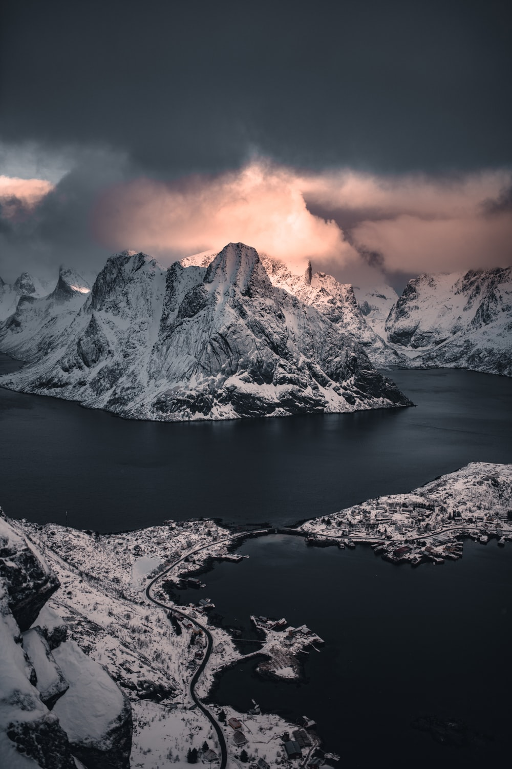 snow covered mountain near body of water during sunset