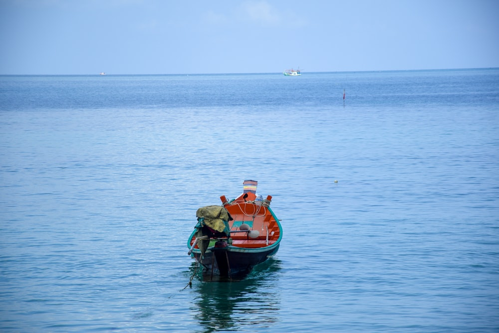 2 men riding on red boat on sea during daytime