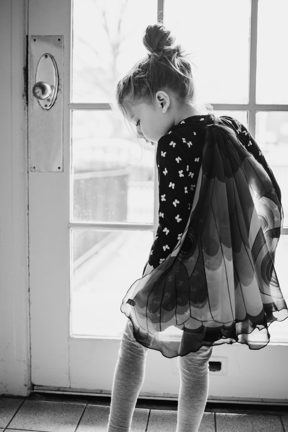 grayscale photo of girl in polka dot dress looking out the window