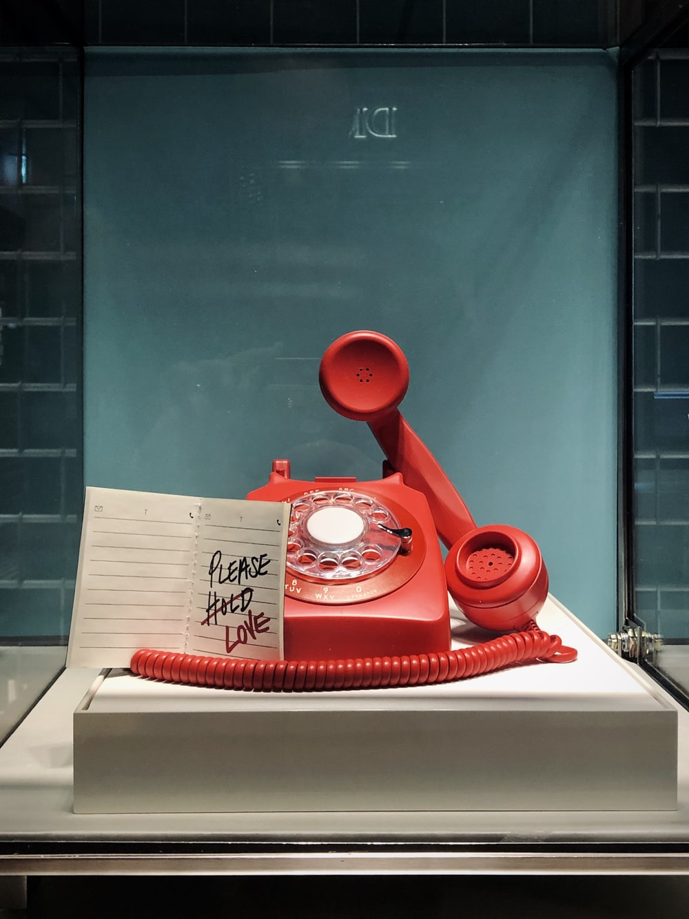 red and white rotary telephone on white table
