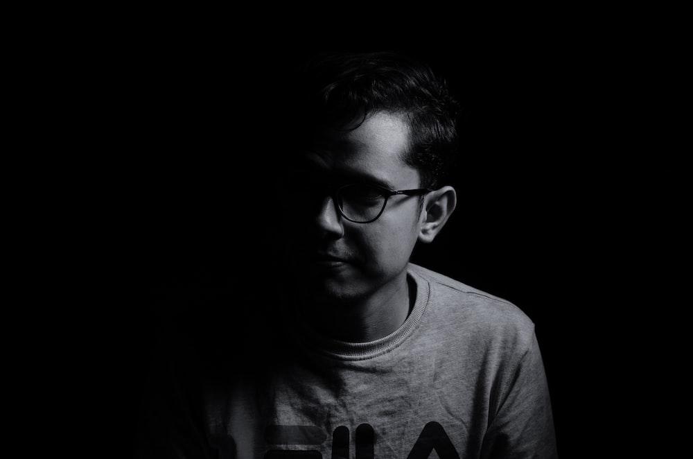 man in crew neck shirt wearing black framed eyeglasses