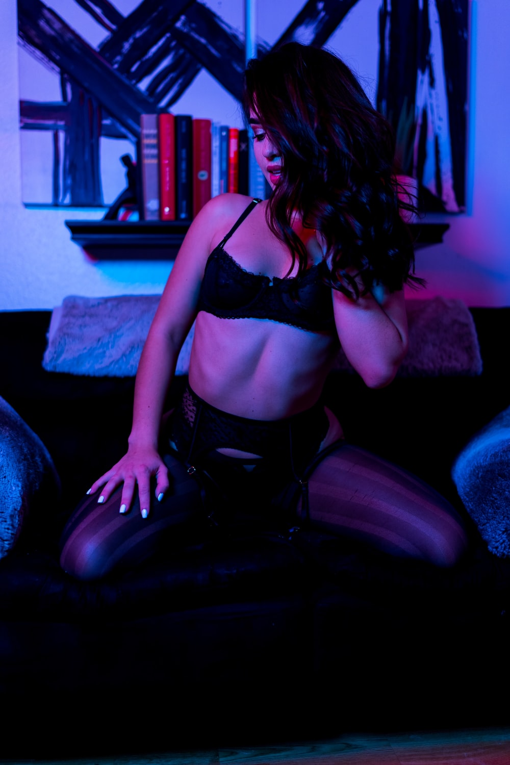 woman in black brassiere and panty kneeling on black leather sofa