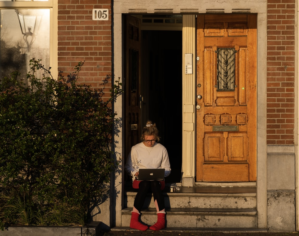 woman in white long sleeve shirt and red pants standing beside brown wooden door