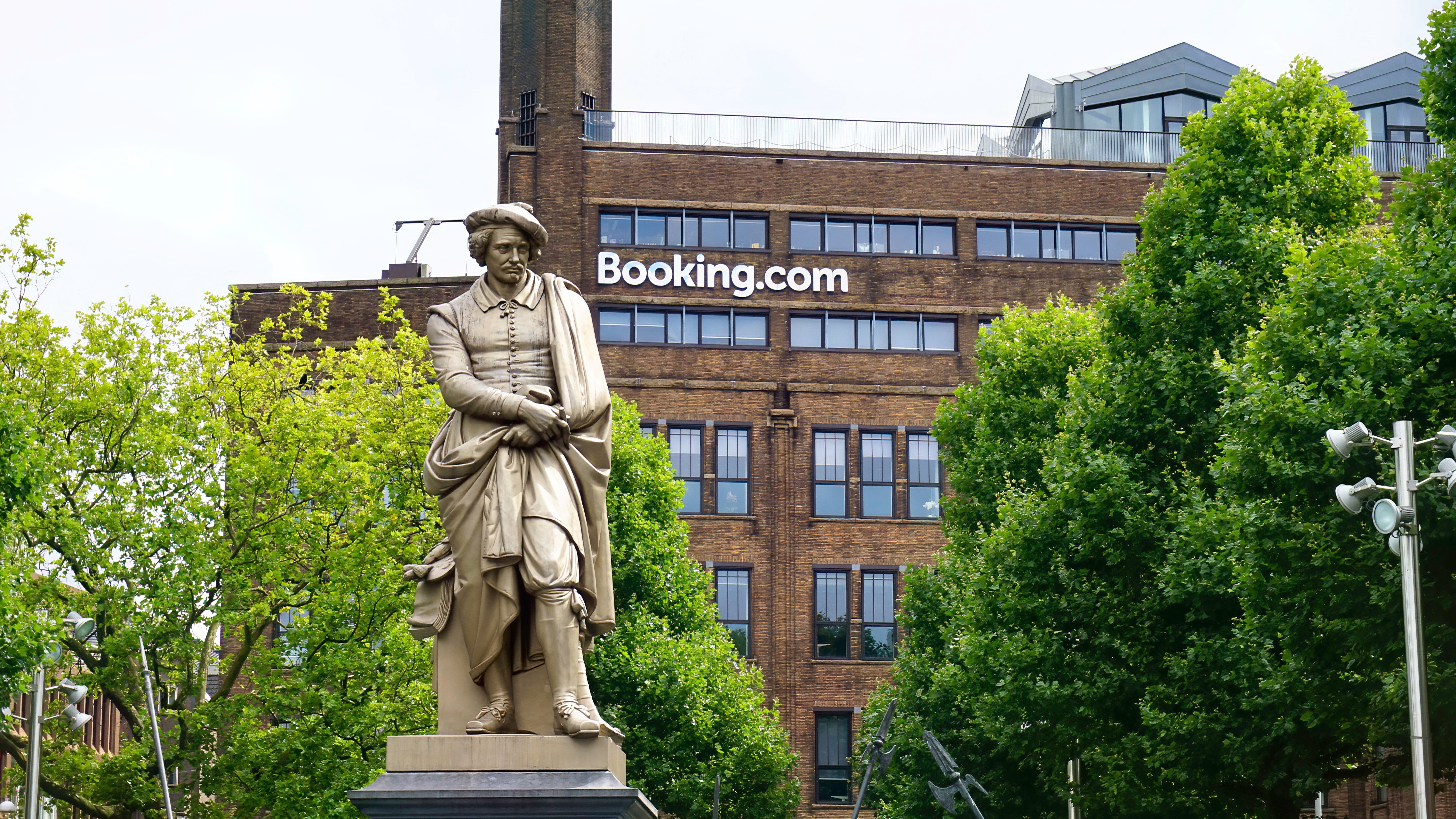 statue of man holding book near brown concrete building during daytime