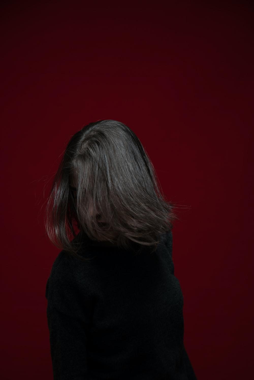 woman in black hoodie standing near red wall
