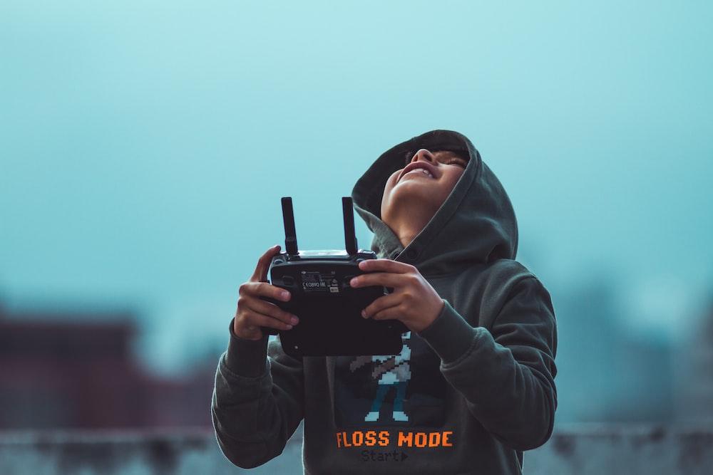 woman in black hoodie holding black dslr camera