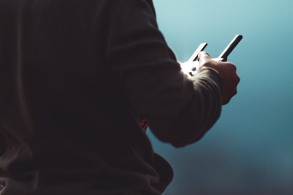 person in black long sleeve shirt holding black pen