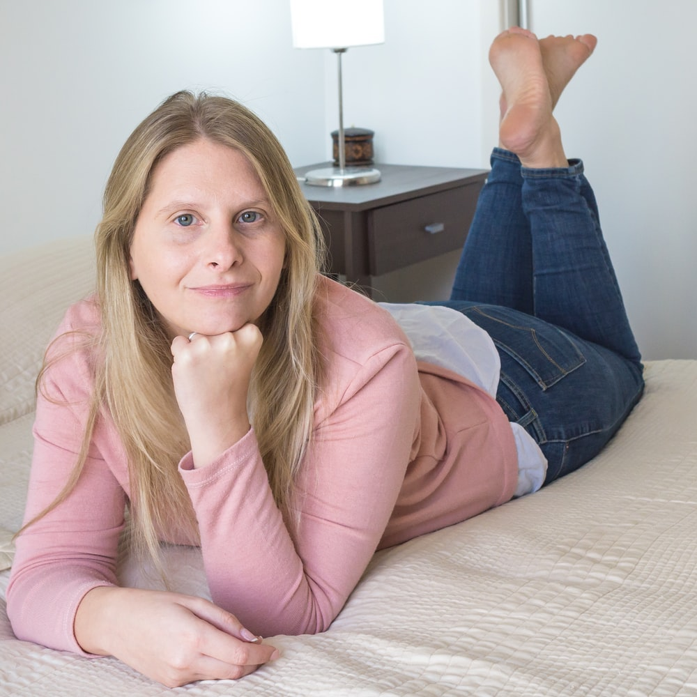woman in pink long sleeve shirt and blue denim jeans sitting on bed