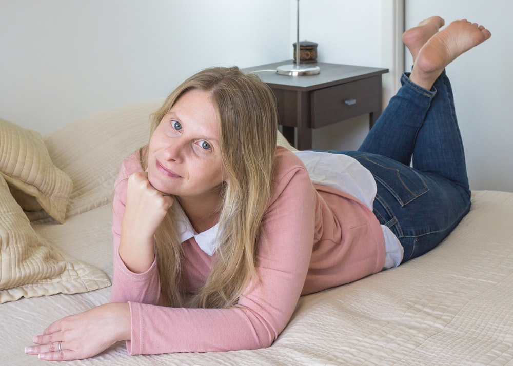 woman in pink long sleeve shirt and blue denim jeans lying on bed