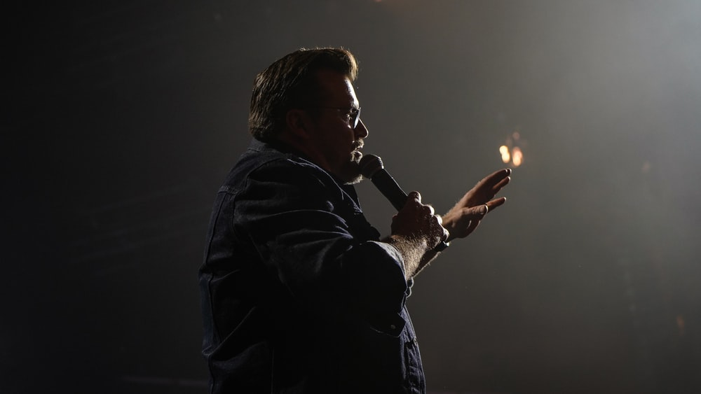 man in black jacket holding microphone