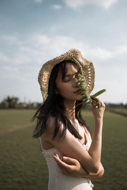 woman in white tank top wearing brown straw hat