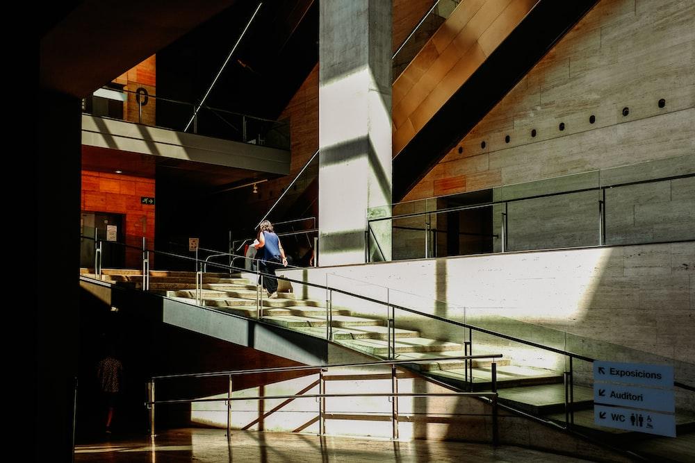 man in blue shirt walking on white concrete staircase