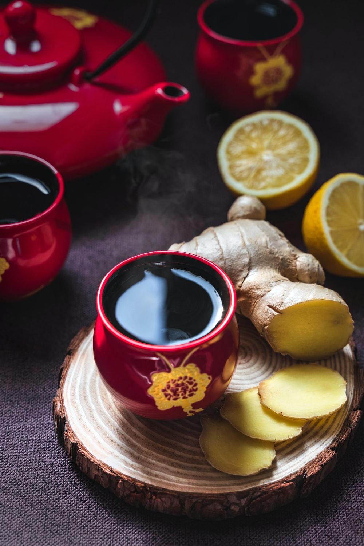 sliced lemon on red ceramic saucer beside red ceramic mug with black liquid
